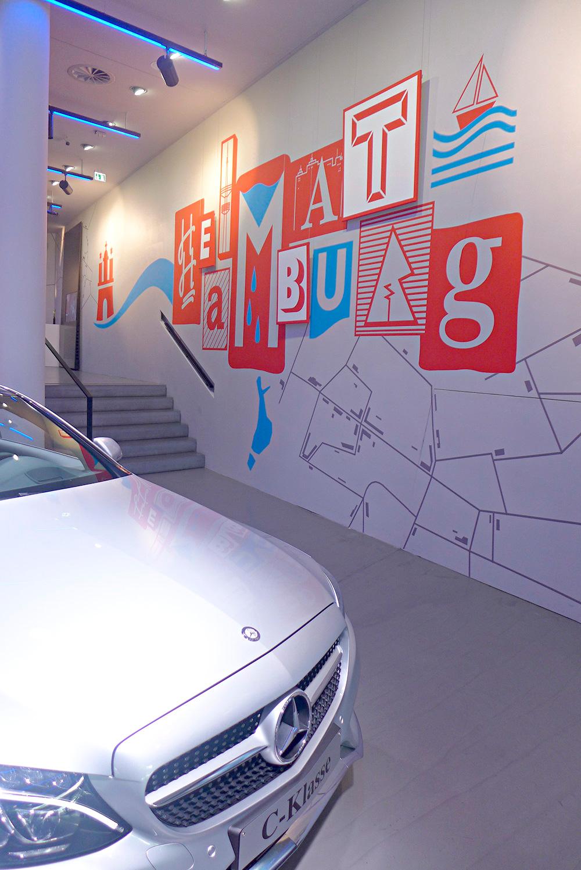 typografische Wandgestaltung im mercedes store hamburg thema heimat